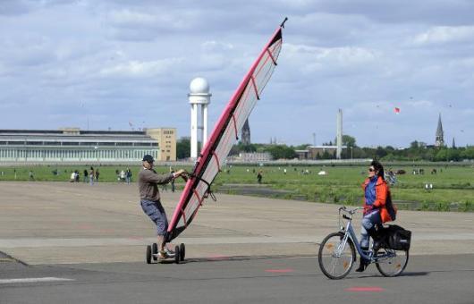 Eine Radlerin und ein Mann mit einem Surfsegel auf Rollen erkunden am Sonntag (16.05.2010) das neu eroberte Flugfeld des Flughafens Tempelhof in Berlin. Auf dem Gelände des einstigen Flughafens Tempelhof ist vor wenigen Tagen Berlins größter Park eröffnet worden. Tausende Besucher nutzen das sonnige Wetter um das 300 Hektar große Areal zu besuchen. Foto: Rainer Jensen dpa/lbn +++(c) dpa - Bildfunk+++null